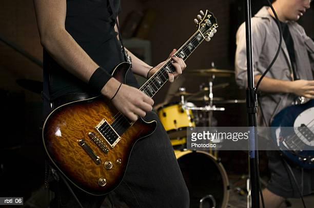 lifestyle portrait of two teenage males as they wildly practice their guitars with a band