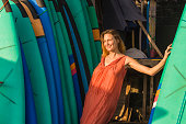 lifestyle portrait of young beautiful and happy blond woman smiling relaxed and cheerful posing with colorful surf boards leaning in surfboard in beauty fashion summer concept