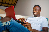 lifestyle portrait of young happy and attractive black African American man using credit card and laptop computer relaxed and cheerful at living room sofa couch internet banking and online shopping