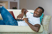 lifestyle portrait of young happy and attractive black afro American man using credit card and laptop computer relaxed and cheerful at living room sofa couch internet banking and online shopping