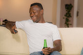 lifestyle portrait young attractive and happy black African American man relaxed at home sofa couch enjoying watching television sports or movie smiling cheerful holding TV remote controller