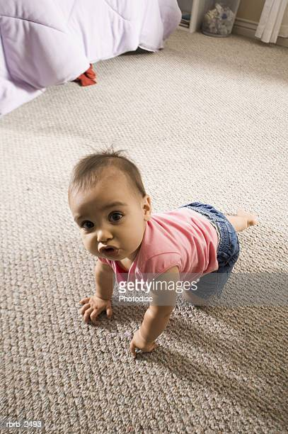 lifestyle shot of a female toddler in a pink shirt as she crawls and looks up at the camera