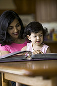 lifestyle shot of a mother as she sits and flips through a photo album with her daughter