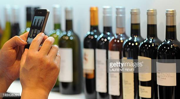 LifestyleAsiaHongKonggastronomywinetrade by Stephen Coates A visitor takes pictures of various bottles of red and white wine during the Vinexpo...