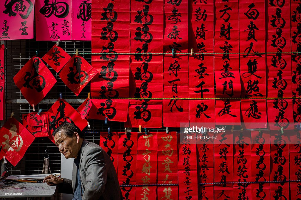 Lifestyle-Asia-offbeat-Lunar, FEATURE by Beh Lih Yi A man sits next to Chinese New Year's calligraphy on red paper displayed in a street of Hong Kong on February 5, 2013. A stock market slide, possible conflict between Japan and China and more Gangnam-styled success for South Korean singer Psy will shape the incoming Year of the Snake, say Asian soothsayers. AFP PHOTO / Philippe Lopez