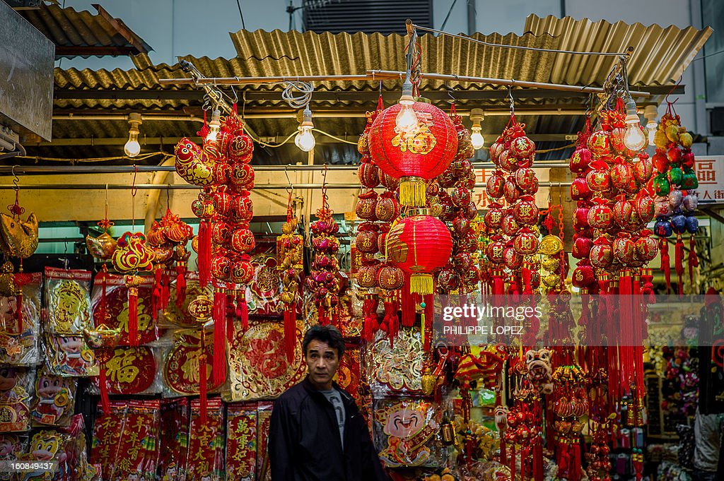 Lifestyle-Asia-offbeat-Lunar, FEATURE by Beh Lih Yi A man walks past a stall selling Chinese New Year decorations at a street market in Hong Kong on February 5, 2013. A stock market slide, possible conflict between Japan and China and more Gangnam-styled success for South Korean singer Psy will shape the incoming Year of the Snake, say Asian soothsayers. AFP PHOTO / Philippe Lopez