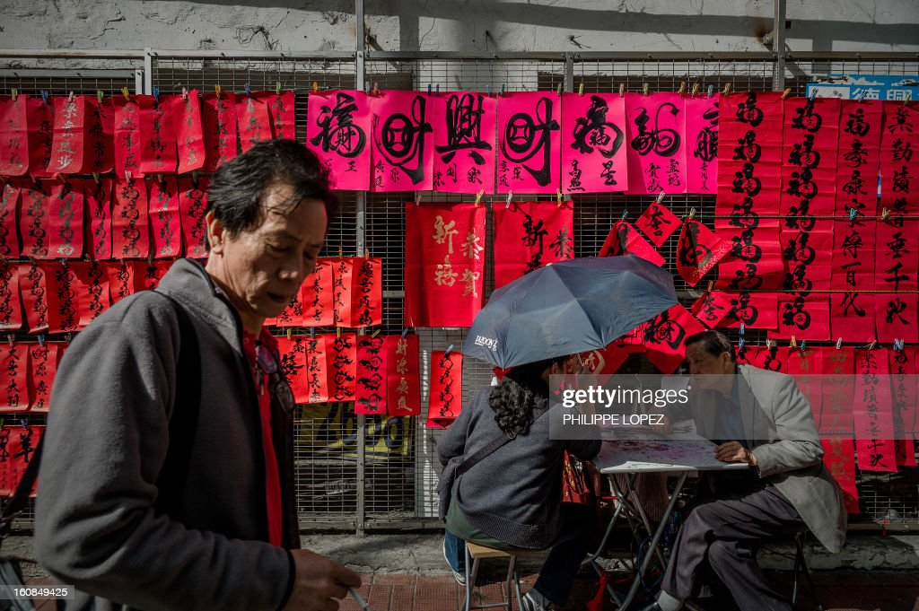 Lifestyle-Asia-offbeat-Lunar, FEATURE by Beh Lih Yi A man walks past Chinese New Year's calligraphy on red paper displayed in a street of Hong Kong on February 5, 2013. A stock market slide, possible conflict between Japan and China and more Gangnam-styled success for South Korean singer Psy will shape the incoming Year of the Snake, say Asian soothsayers. AFP PHOTO / Philippe Lopez