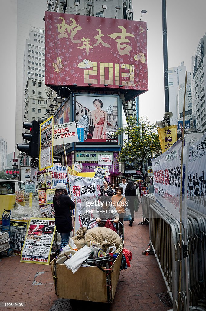 Lifestyle-Asia-offbeat-Lunar, FEATURE by Beh Lih Yi A woman pushes a loaded cart past a billboard set up for the Chinese New Year of the snake in Hong Kong on February 5, 2013. A stock market slide, possible conflict between Japan and China and more Gangnam-styled success for South Korean singer Psy will shape the incoming Year of the Snake, say Asian soothsayers. AFP PHOTO / Philippe Lopez