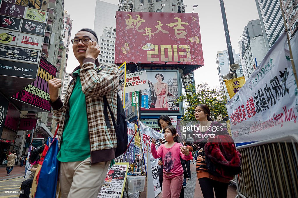 Lifestyle-Asia-offbeat-Lunar, FEATURE by Beh Lih Yi Pedestrians walk past a billboard set up for the Chinese New Year of the snake in Hong Kong on February 5, 2013. A stock market slide, possible conflict between Japan and China and more Gangnam-styled success for South Korean singer Psy will shape the incoming Year of the Snake, say Asian soothsayers. AFP PHOTO / Philippe Lopez