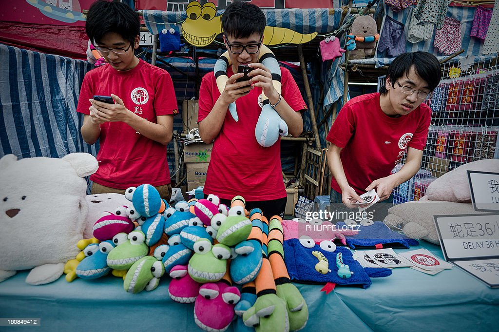 Lifestyle-Asia-offbeat-Lunar, FEATURE by Beh Lih Yi Youths check their phones as they stand at a stall of a Chinese New Year fair in Hong Kong on February 5, 2013. A stock market slide, possible conflict between Japan and China and more Gangnam-styled success for South Korean singer Psy will shape the incoming Year of the Snake, say Asian soothsayers. AFP PHOTO / Philippe Lopez