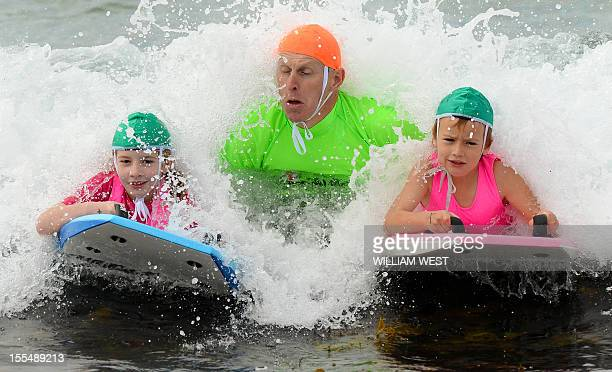 LifestyleAustralialifesavingFEATURE by Madeleine Coorey A lifesaver instructs two young girls on boogie boards as they participate in what is called...