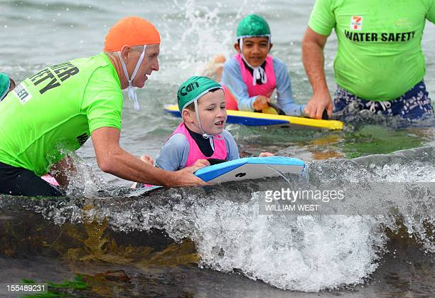 LifestyleAustralialifesavingFEATURE by Madeleine Coorey A lifesaver instructs two young boys on boogie boards as they participate in what is called a...