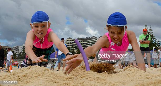 LifestyleAustralialifesavingFEATURE by Madeleine CooreyYoung children dive to grab the pegs as they participate in what is called a surf lifesaving...