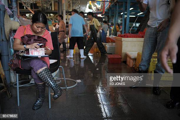 LifestylefoodenvironmentfishworldHongKongFEATURE by Lawrence Bartlett This photo taken on September 27 2009 shows a woman counting currency as fish...