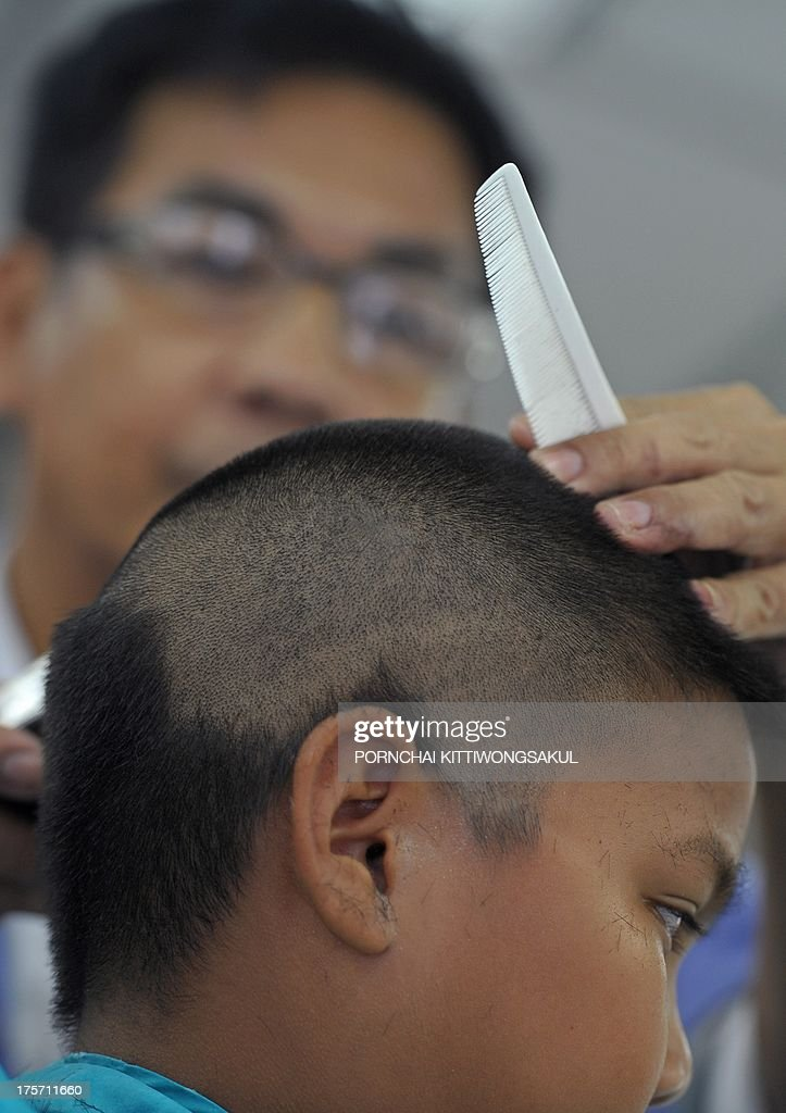 Lifestyle-hair-Thailand,FEATURE by Apilaporn VECHAKIJ This photo taken on July 31, 2013 shows a Thai barber (top) shaving the head of student at a hairdresser's shop near a school in Bangkok. Rules issued in 1972 compelled Thai pupils to have identical hairstyles -- a trim not below the earlobes for girls and a maximum five-centimetre length for boys -- until the end of high school. But students are now hoping to flaunt their individuality after an edict by Thailand's education ministry in May scrapped the measure.