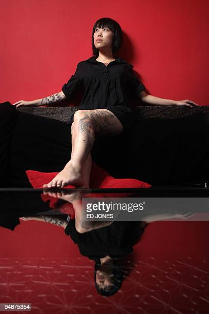 LifestyleHongkongwomentattoos by Ed Jones Tattoo artist Joey Pang poses in her shop the Tattoo Temple in Hong Kong on October 24 2009 Hiding behind...