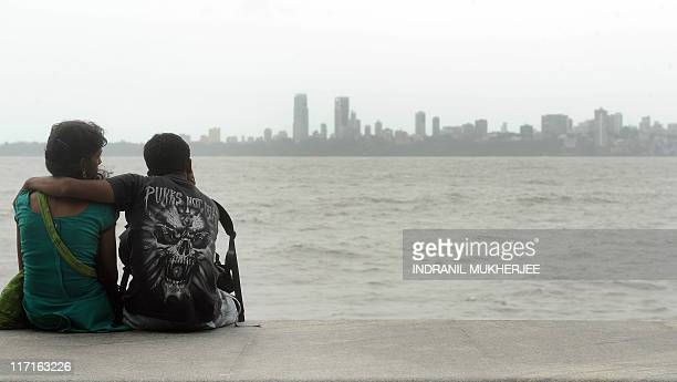 LifestyleIndiacityMumbaiFEATURE by Phil Hazlewood An Indian couple sits on the promenade overlooking the Arabian Sea off the city's iconic 'Queens...