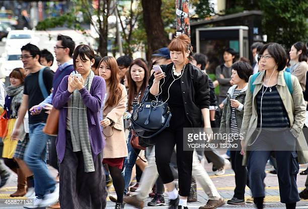 LifestyleJapansmartphonestechnologywalkingFEATURE BY ALASTAIR HIMMER This picture taken on November 3 2014 shows pedestrians using their smartphones...