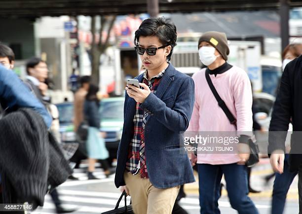 LifestyleJapansmartphonestechnologywalkingFEATURE This picture taken on November 3 2014 shows a pedestrian using his smartphone on a street in Tokyo...