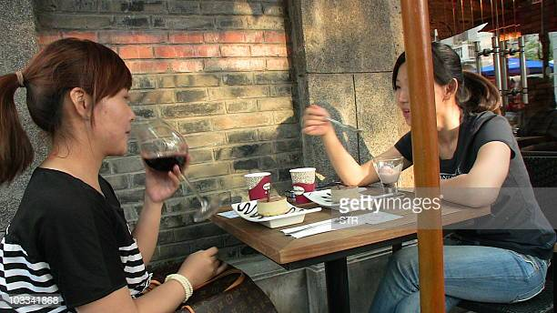 LifestylewineChinaurbanFEATURE An undated photo shows two Chinese women eating ice cream with wine in the trendy Xintiandi district of wellheeled...