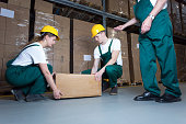 Two young workers lifting heavy box in warehouse