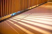 Sunlight through the wooden lath causes to shade of Light and shadow on the marble floor