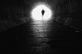 Dark tunnel with light end. Silhouette man on the end.