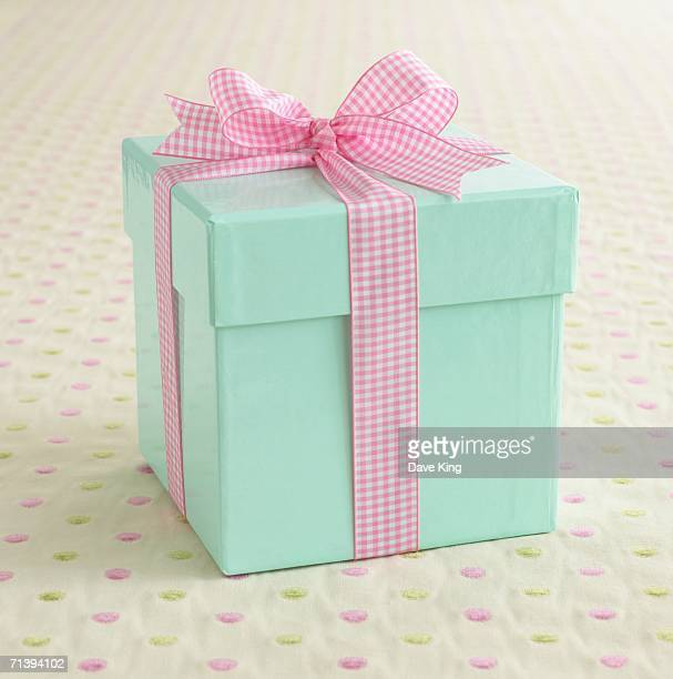 A light blue box wrapped with a pink ribbon.