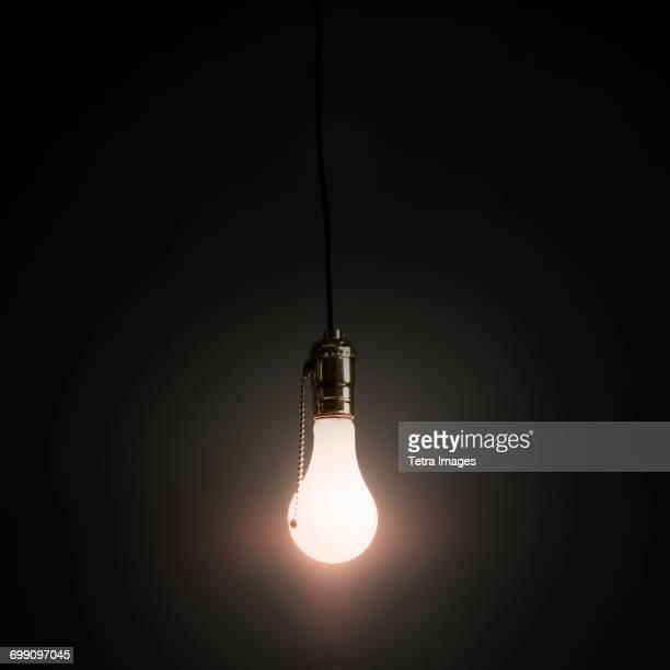 Light bulb hanging against grey background