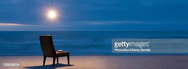 Light bulb illuminated over chair on beach at night