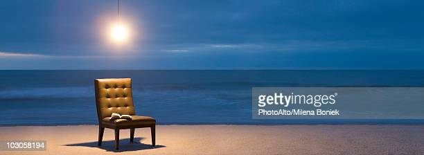 Light bulb illuminated over chair with open book on beach at night