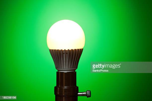 LED Light Bulb in Lamp Socket with Green Background