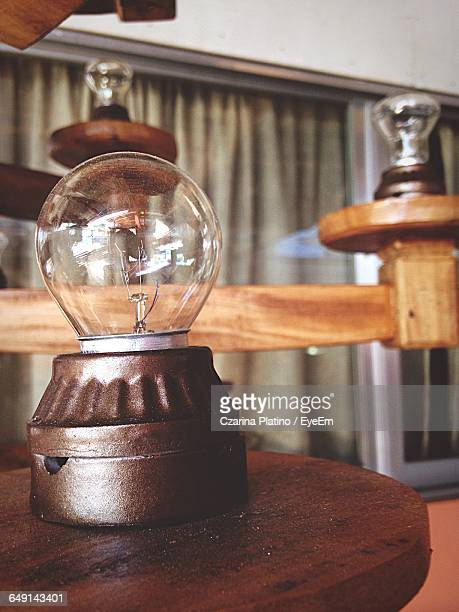 Light Bulb On Wooden Table At Home