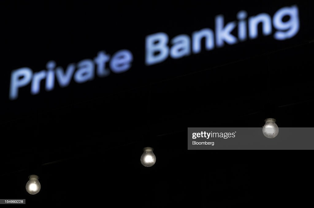 Light bulbs are seen underneath a Private Banking sign outside the Bank Hapoalim (Switzerland) Ltd. (BHI) offices in Geneva, Switzerland, on Monday, Oct. 29, 2012. Geneva's banks employed 502 fewer people at the end of June compared with a year earlier as foreign wealth managers cut jobs and shifted employees to other locations, a survey by the city's financial lobby group shows. Photographer: Valentin Flauraud/Bloomberg via Getty Images