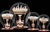 Photo of light bulbs with shining fibres in IDEA, VISION, CONCEPT and CREATIVITY shape on black background