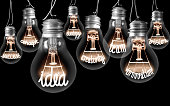 Photo of light bulbs with shining fibers in a shape of IDEA concept related words isolated on black background