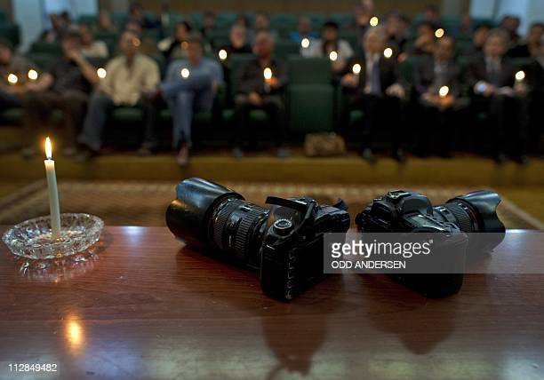 A light burns next to two cameras posed symbolicallly during a memorial service for slain photojournalists Tim Hetherington and Chris Hondros held in...