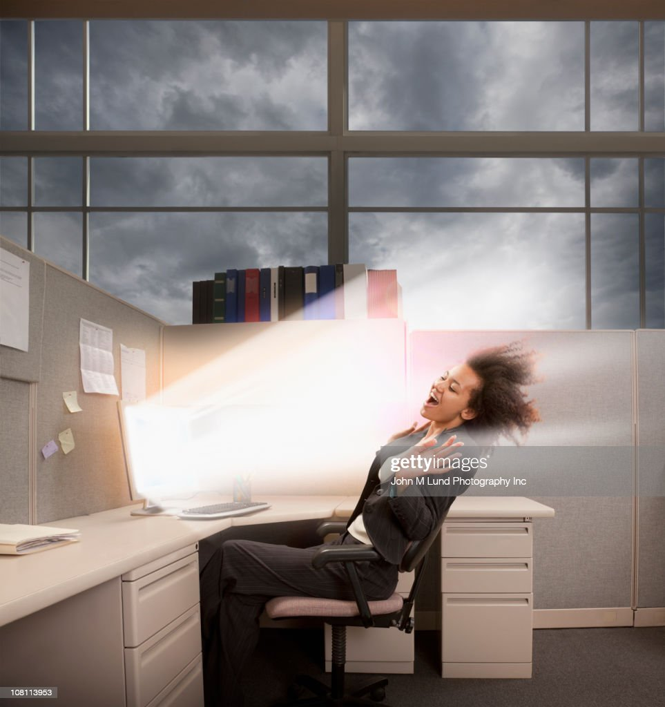 Light bursting from computer at mixed race businesswoman : Stock Photo