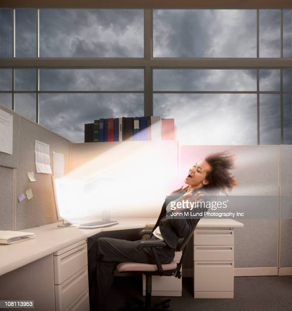Light bursting from computer at mixed race businesswoman