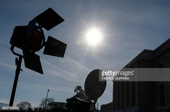 Light camera and satellite dish are silhouetted against the sun on the eve of resumption of peace talks on Syria on February 22 2017 at the United...