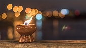 Light candle with hot fire burning brightly in blur dark black waterfront riverfront reflective wavy ripple tide background
