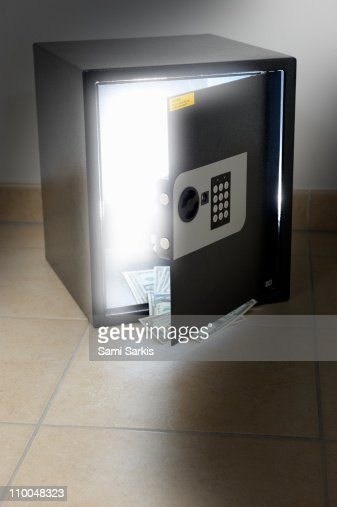 Light coming out a safe, US banknotes at door edge