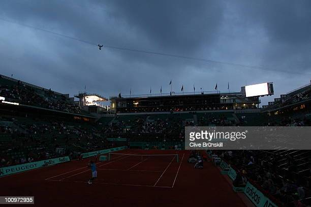 Light from a scoreboard and a television studio illuminate the court as Gael Monfils of France serves in darkness during the men's singles second...