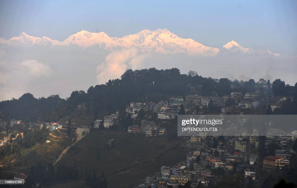 Light from a sunrise is cast on mountain Kangchenjunga near Darjeeling (bottom) on December 22, 2012. Kangchenjunga is the third highest mountain in the world with an altitude of 8,586 metres (28,169 feet) after Mount Everest and K2. The economy of the eastern Indian state of Sikkim is being buoyed by the ever increasing numbers of foreign and domestic tourists keen to view the peak which sits at the eastern end of the Himalayan Mountain Range. AFP PHOTO/ Diptendu DUTTA