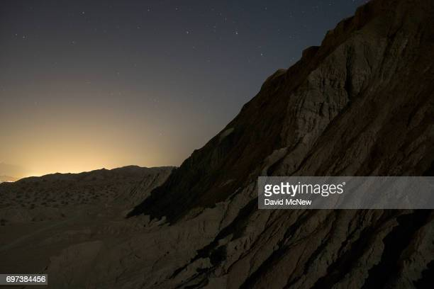 Light from Palm Springs area cities shines in the distance behind a landscape contorted by the San Andreas Fault in the Mecca Hills in the predawn...