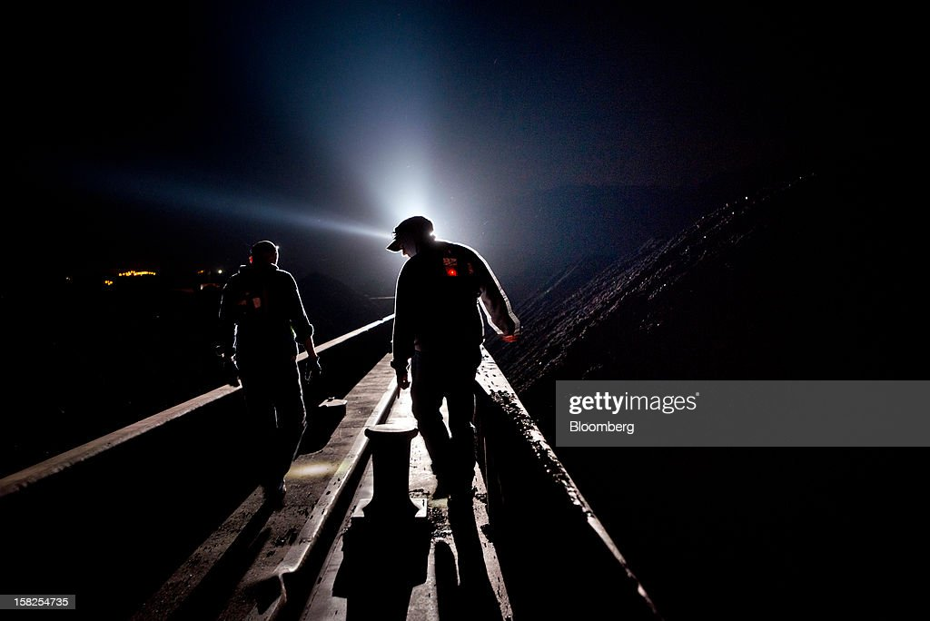 'BEST PHOTOS OF 2012' (): A light from the American Electric Power Co.'s AEP Leader towboat silhouettes deck hands as they walk on barges loaded with 30,000 tons of coal during watch on the Ohio River near Wheeling, West Virginia, U.S., on Tuesday, Oct. 23, 2012. Coal demand in the U.S. increased 3.7 percent last week, led by a gain in the East. Photographer: Ty Wright/Bloomberg via Getty Images