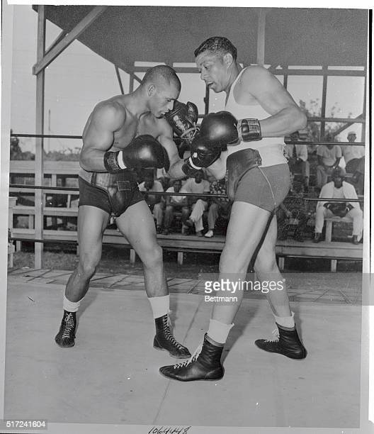 Light heavyweight Harold Johnson who'll meet Champion Archie Moore in Madison Square Garden for the title on August 11th spars with his father Phil...