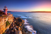 Sunrise seascape and red-white lighthouse.