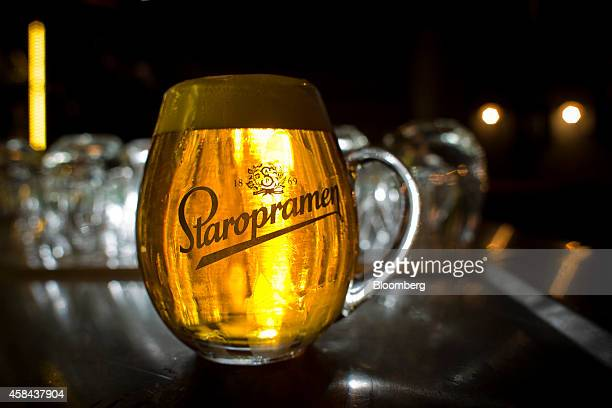 Light illuminates a glass mug of Staropramen beer in the visitor's center restaurant at the Pivovary Staropramen AS brewing company operated by...