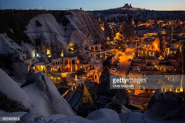 Light illuminates cave hotels at sunset in the town of Goreme on April 17 2016 in Nevsehir Turkey Cappadocia a historical region in Central Anatolia...